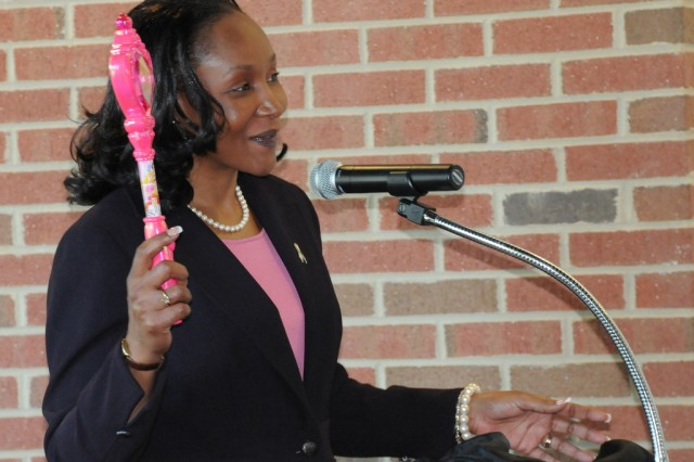 Retired Command Sgt. Maj. Michele S. Jones, special assistant to the Secretary of Defense White House Liaison, holds her wand to the audience during the Women's History Month Program at the U.S. Army Women's History Museum on Fort Lee, Va., March 19. She used the prop to illustrate her wish to help write women into history.