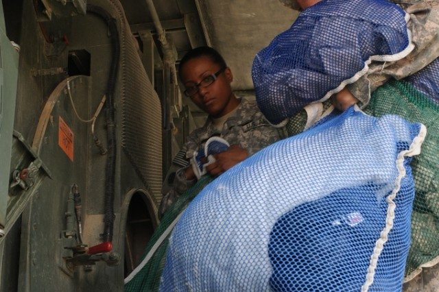 Spc. Hannah R. Perez, an equipment repair specialist and an El Paso, Texas, native, and Spc. Paola N. Gonzalez, a shower, laundry and renovations specialist and a Whittier, Calif., native, both with the 263rd Quartermaster Company, 541st Combat Sustainment Support Battalion, 15th Sustainment Brigade, 13th Sustainment Command (Expeditionary), retrieve laundry from the Laundry Advanced System March 13 at Contingency Operating Base Taji, Iraq.