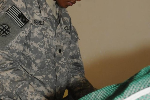 Spc. Hannah R. Perez, an equipment repair specialist with the 263rd Quartermaster Company, 541st Combat Sustainment Support Battalion, 15th Sustainment Brigade, 13th Sustainment Command (Expeditionary) and an El Paso, Texas, native, folds laundry during training March 13 at Contingency Operating Base Taji, Iraq.