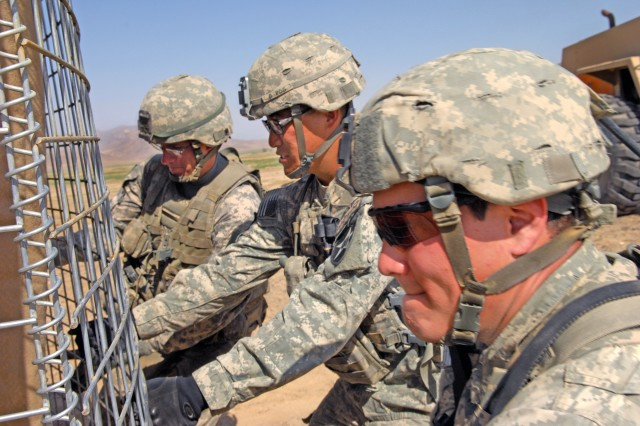 Soldiers install HESCO barriers at an Afghan police checkpoint in Robat, Afghanistan, March 19, 2010. The Soldiers are assigned to the 2nd Infantry Division's 5th Stryker Brigade Combat Team.