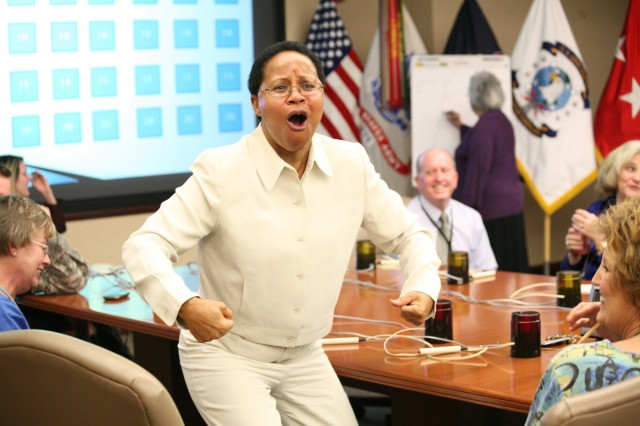 Juanita Sales Lee flexes her muscles to prove her intellectual superiority after her team, the CIO-G6 team, won the U.S. Army Space and Missile Defense Command/Army Forces Strategic Command's Women's History Jeopardy Contest March 23.