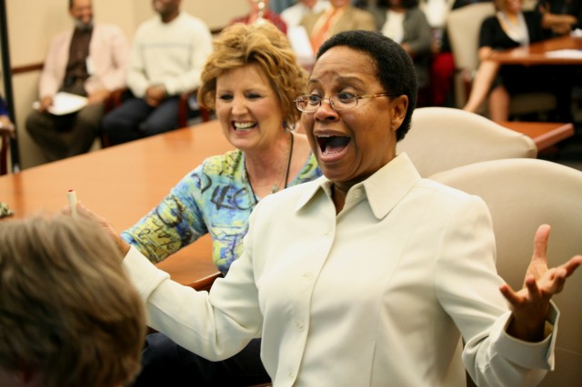 Juanita Sales Lee is excited about getting an answer correct during the U.S. Army Space and Missile Defense Command/Army Forces Strategic Command's Women's History Jeopardy Contest March 23. Her teammate, Sharon DeLozier, is behind her.