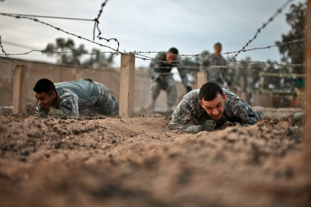 CAMP TAJI, Iraq - During a team-building challenge, 1st Lt. Alan Roy (right), a platoon leader from Strawberry, Minn., and Sgt. Luis Garcia, a squad leader from Bryant, Texas, both of whom are in Company F, 3rd Battalion, 227th Aviation Regiment, 1st Air Cavalry Brigade, 1st Cavalry Division, U.S. Division-Center, low-crawl through an obstacle course March 23. The two Soldiers' teams endured six other events after completing the obstacle course.