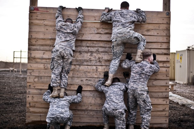"""CAMP TAJI, Iraq - Trying to get a quick time through the obstacle course, Soldiers from Company F, 3rd Battalion, 227th Aviation Regiment, 1st Air Cavalry Brigade, 1st Cavalry Division, U.S. Division-Center, form """"steps"""" with their bodies to get over a wooden barrier March 23. The Soldiers were tested physically and mentally throughout the day."""