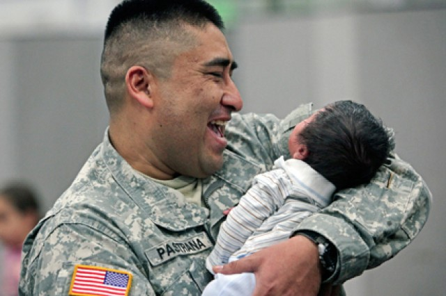 First Lt. Herrera Pastrana enjoys holding infant Antonelly White March 20 as Soldiers from the 328th Human Resources Company and the 363rd Quartermaster Battalion are honored at Fort Sam Houston after their return home from Afghanistan.