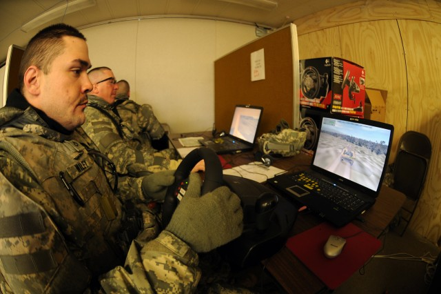 Pfc. Dana Wiley drives a simulated Humvee guntruck from the laptop computer of the DARWARS program in a classroom at Contingency Operating Location Freedom at Fort McCoy, Wis. To Wiley's left is Sgt. Jason Crawley, operating the truck commander's position, and, to Crawley's left, with back to camera, Spc. Matthew Barr, at the turret gunner position.