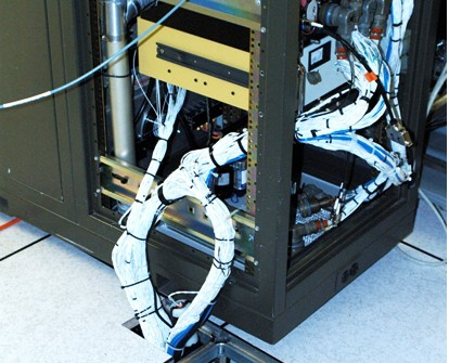 A 78-pound MRT Cable Harness descends below the floorboards of the research lab at Camber Corporation in Research Park, snaking between the two sections of the test machine. The test setup will eventually be on-board the Armys Apache attack helicopter.
