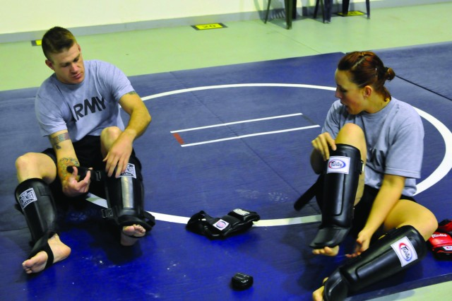 Staff Sgt. Michael Rider and Sgt. Autumn Richardson don their gear before a sparring match.