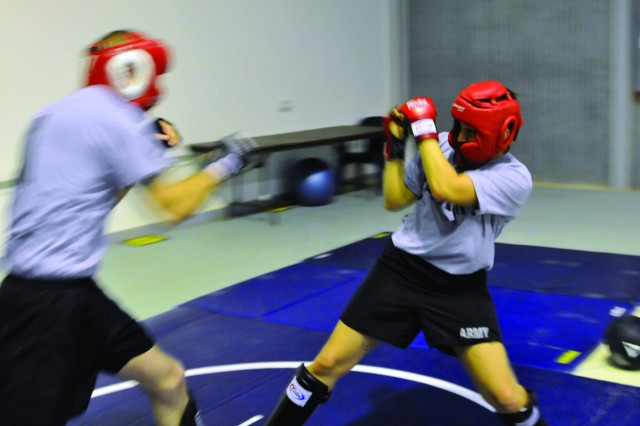 Sgt. Autumn Richardson, puts her hands up in a defensive position as Staff Sgt. Michael Rider throws a right-hand punch.