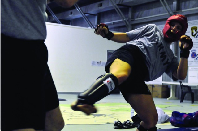Sgt. Autumn Richardson throws a kick toward Staff Sgt. Michael Rider, during a friendly bout.