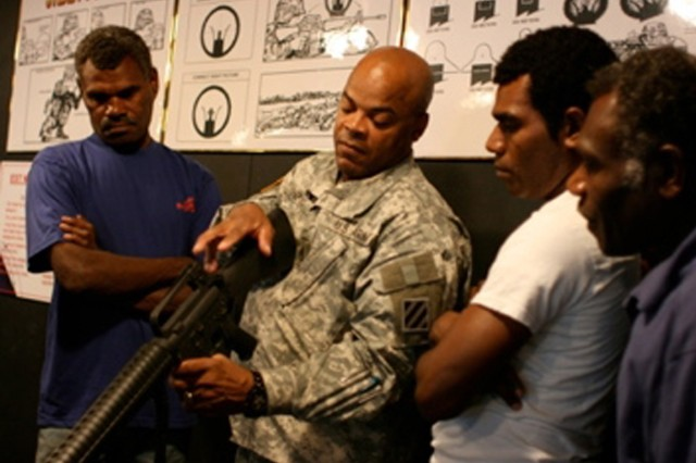 """Staff Sgt. Steve Shepard of the 3rd Infantry Division shows Pacific Islanders how to use a weapon. He welcomed them to his home as part of the Travel Channel's """"Meet the Natives: USA"""" series."""