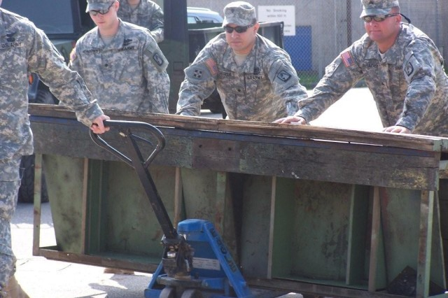 Spc. Glenn Meadows, Spc. Juan Varela and Sgt. Danny Braden of 412th Aviation Support Bn., move scrap metal for recycling as part of Operation Jenny Craig in Ansbach, Germany.