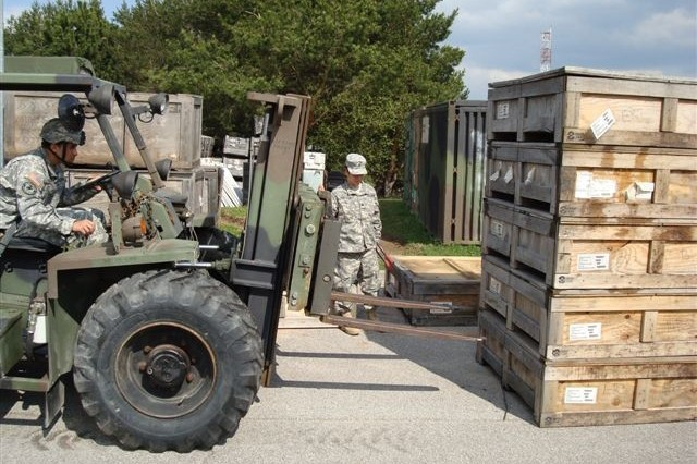 Soldiers in Company A 412th Aviation Support Bn. remove crates of ring mounts off a trailer for inventory during Operation Jenny Craig, in Ansbach, Germany.