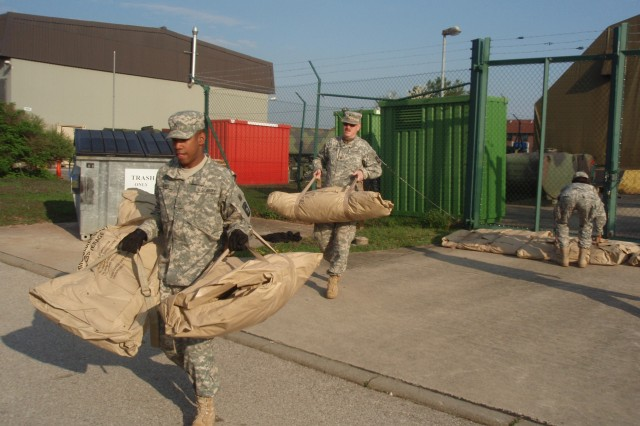 Soldiers of the 412th Aviation Support Battalion, 12th Combat Aviation Brigade, in Ansbach, Germany, transport camouflage nets to storage. The nets were placed back into inventory during Operation Jenny Craig.