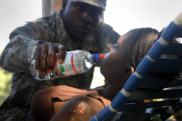 Staff Sgt. Junior Florestal gives his cousin, Sonia Catilius, a drink of water. A cook with the 82nd Airborne Div., Florestal is a Haiti native serving as a translator with the medical team.