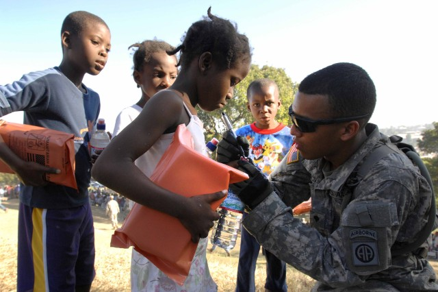 Spc. Juan Valencia marks the fingernail of a Haitian child to indicate she has gone through a food and water distribution line in Port-au-Prince, Haiti, Jan. 18. Valencia is with the 1st Squadron, 73rd Cavalry Regiment, 2nd Brigade Combat Team, 82nd Airborne Division. The squadron established a forward operating base and passed out thousands of meals and bottles of water.