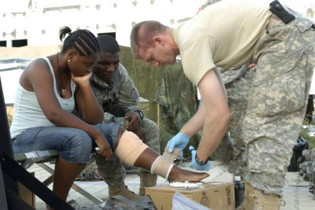 Capt. Jason Ferguson, 2nd BCT, 82nd Abn. Div., brigade surgeon, wraps clean gauze around a Port-au-Prince woman's leg injury as Sgt. 1st Class Dominique Michel, 2nd BCT, translator, translates instructions on the proper care of the injury, Jan. 25.