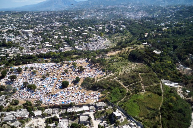 An aerial view of a tent city for displaced Haitians near a landing zone for aid distribution.