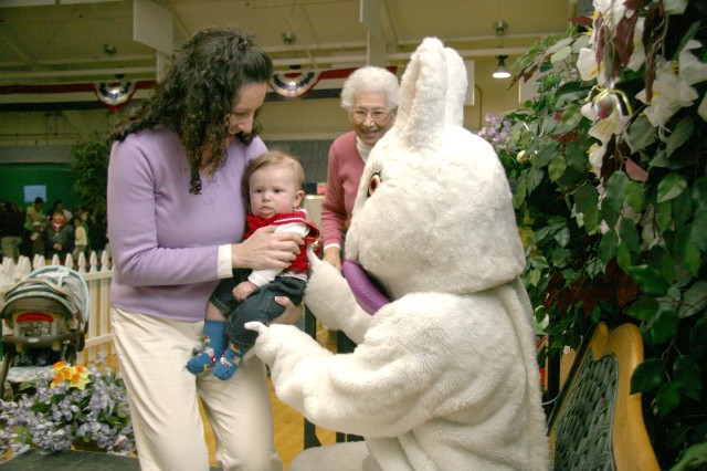 FORT CARSON, Colo.-Family member Michelle Nowak hands four-and-a-half month old son Lucas to the Easter Bunny as her mother, Leta Vitanov, looks on. Nowak said the photo with the Easter Bunny would be sent to Lucas' father who is currently deployed.