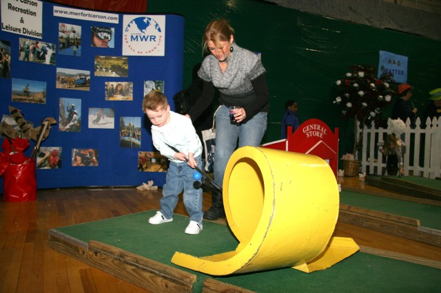 FORT CARSON, Colo.-Drake Murray, 4, takes a swing at the Queen of Hearts Castle miniature golf as his mother, Heather Murray, looks on.