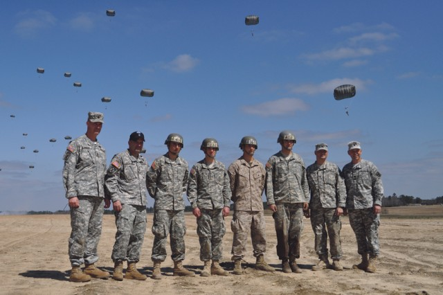 Members of the command team from 1st Battalion (Airborne), 507th Parachute Infantry Regiment, pose with the Airborne students who jumped first with the new T-11 parachute. Based on the original parachute test platoon, predecessor of the 501st Parachute Infantry Battalion, the first jump students were chosen by lottery. Pictured from left are C Company first sergeant, 1st Sgt. Christopher Goodrow; battalion command sergeant major, Command Sgt. Maj. Chippy Mezzaline; Pfc. Rincon Santos; Pfc. Jonathan Whitley; Marine Cpl. David Chapman; 2nd Lt. Charles Lesperance; C Company commander, Capt. Dean Gibson and battalion commander, Lt. Col. Jon Ring.