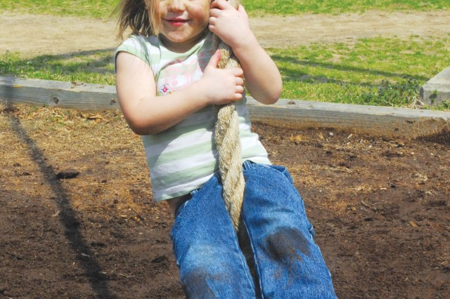Three-year-old Rayna Smith plays on the practice swing, a rope basic trainees use to swing across a blocked-off area that represents water.  Rayna was one of more than 70 family members who attended Jane Wayne Day Saturday on Sand Hill.