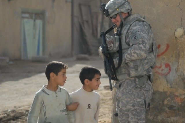 Sgt. Jacob Lappin, a civil affairs noncommissioned officer attached to Company C , 1st Battalion, 15th Infantry Regiment, 3rd Heavy Brigade Combat Team, 3rd Infantry Division, smiles as two Iraqi boys pass him on the streets of Najaf, Iraq, March 7, 2010.  Lappin was part of an escort team taking neutral U.N. observers to various polling sites in the area.