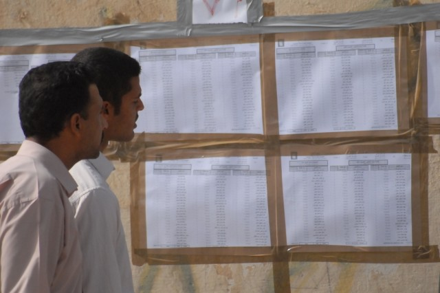 Two Iraqi men search a voters list for their names before going into a polling station in Najaf, Iraq, March 7, 2010.  The parliamentary election is the second time Iraqi citizens have taken part in a national national election since the overthrow of Saddam Hussein.