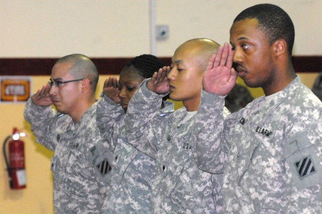 Soldiers assigned to the 1st Battalion, 10th Field Artillery Regiment, 3rd Heavy Brigade Combat Team, 3rd Infantry Division, salute the memorial stands of Sgt. Aaron Arthur and Sgt. Lakeshia Bailey during a memorial ceremony at Contingency Operating Station Delta, Iraq, March 12, 2010. Arthur and Bailey died from injuries sustained during a vehicle rollover several days before.