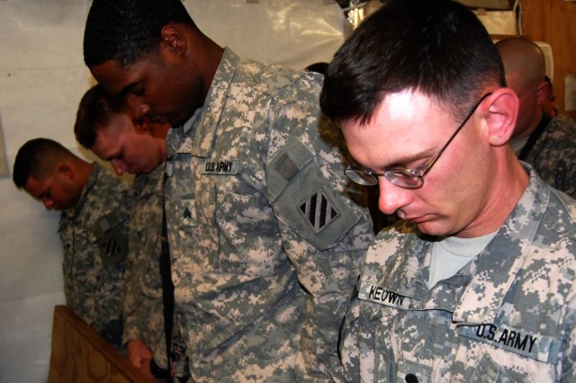Soldiers assigned to the 2nd Battalion, 69th Armor Regiment, 3rd Heavy Brigade Combat Team, 3rd Infantry Division, bow their heads in prayer during the memorial ceremony for Spc. Mike Snelgrove at Contingency Operating Station Kalsu, Feb. 12, 2010.  Snelgrove, a combat medic assigned to Headquarters Company, 2-69 Armor Regt., died unexpectedly back at home on the first day of his mid-tour leave.