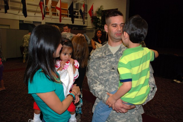 Sgt. Peter Longoria of the 14th Military Intelligence Battalion greets his Family after returning to Fort Sam Houston from Iraq March 16. His battalion deployed in support of Operation Iraqi Freedom in July 2009.