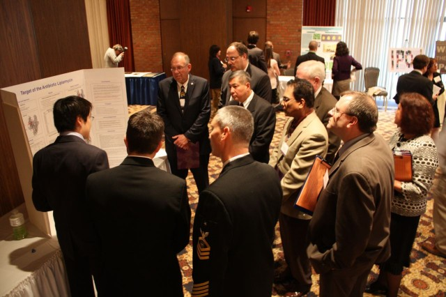 Symposium judges from Department of Defense, industry and academia listen to the poster presentation of Richard Y. Ebright at Fort Monmouth's Gibbs Hall March 25.