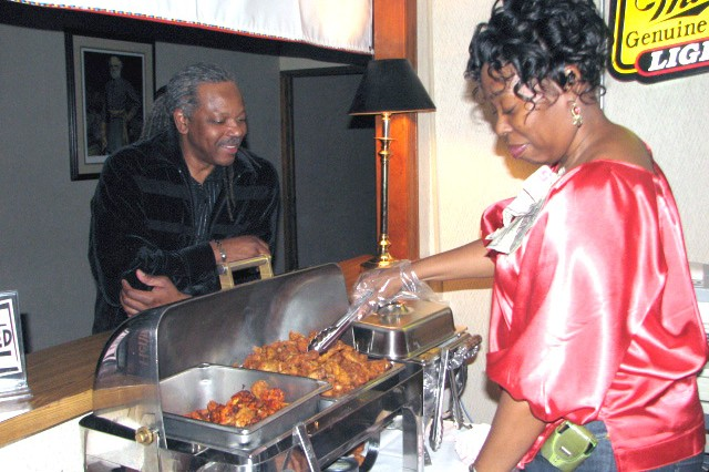 "Simone Smith, a hostess at the Fort Gillem Getaway club, hands Will Sansbury, a truck driver with S&S Expedite Service, Atlanta, some wings during the ""Blue Lights in the Basement"" old school jam at the club March 19. The dance is held on the third Friday of each month and features music from the 70s and 80s."