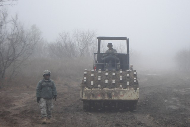 FORT BLISS, Texas - Pvt. Burney Johnson guides Pfc. Edwin Cotto as he operates a vibratory roller with sheep's foot attachment during an early morning fog.  Soldiers from 94th Engineer Battalion Soldiers, which is based out of Fort Leonard Wood, Mo., constructed approximately a mile of all-weather gravel road to be used by U.S. Border Patrol agents patrolling the U.S.-Mexico border near Laredo.