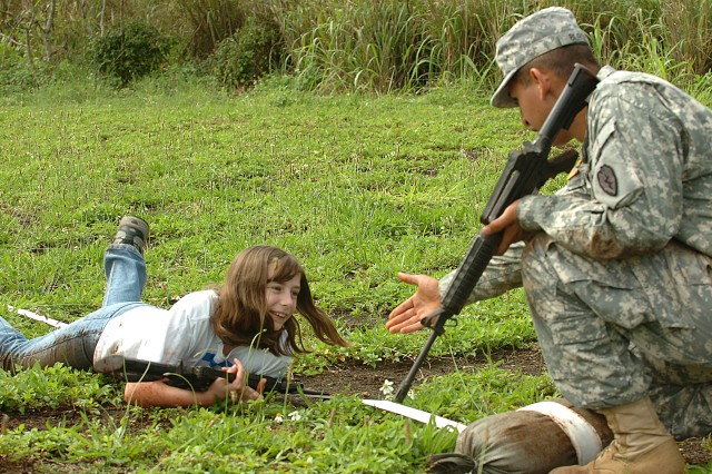 Isabella Berry (left) of Team Blue low crawls through the grass to lane aid Pvt. Johnathan Biurquis, 2nd Squadron, 6th Cavalry Regiment, 25th Combat Aviation Brigade, while gripping onto a rubber training version of an M-4 Carbine Rifle as part of the individual movement tactics challenge of the 2-6 CAV Spur Ride held at Wheeler Army Airfield, March 26. The event allowed children of 25th CAB Soldiers to get together for fun, games and a little military experience with several physical challenges throughout the day's event. The individual movement tactics challenge tasked participants with a 50-meter low crawl and movement-under-fire drills, which challenged the children physically and familiarized them with basic military combat techniques. More than 40 children participated in the day's events and each earned an honorary induction into the cavalry's prestigious Order of the Spur. (U.S. Army photo by Spc. Jesus J. Aranda, 25th Infantry Division Public Affairs Office)