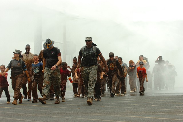 Sergeant Elvia Davila (left), team leader of Team Blue; Sgt. Aaron Nefe (center), team leader for Team Red, and Sgt. Brian Jarrell (right), team leader for Team Orange, all Soldiers with the 2nd Squadron, 6th Cavalry Regiment, 25th Combat Aviation Brigade, lead their teams through a downpour of water courtesy of the Wheeler Army Airfield Fire Department following the final event, a road march, of the 2-6 CAV Spur Ride held at Wheeler Army Airfield, March 26. The event allowed children of 25th CAB Soldiers to get together for fun, games and a little military experience with several physical challenges throughout the day's event. The water served to not only cool down the event's participants on a warm day, but also wash away much of the infamous red Hawaiian mud which had been caked onto their clothing following the event. More than 40 children participated in the day's events and each earned an honorary induction into the cavalry's prestigious Order of the Spur. (U.S. Army photo by Spc. Jesus J. Aranda, 25th Infantry Division Public Affairs Office)