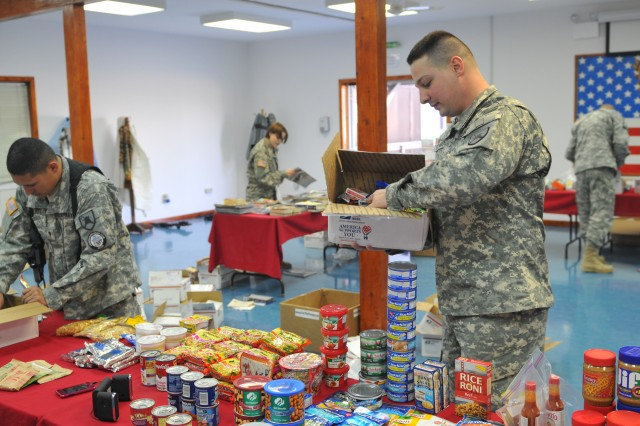 "Spc. Timothy E. Stewart, Manhattan, Kan., and Spc. Daniel T. Teviet, Grand Forks, N.D., help set up items for a Soldiers pantry. The idea started with the ""Defender"" JEC, but to assist more Soldiers they included ""Falcon"" and LMT JEC to support this large event."