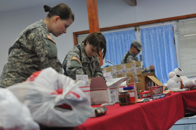 Spc. Callie C. Craddock, Fargo, N.D. and Spc. Brittany Allen, Mandan, N.D., organize items prior to a battle group-wide Soldier's Pantry held March 21.