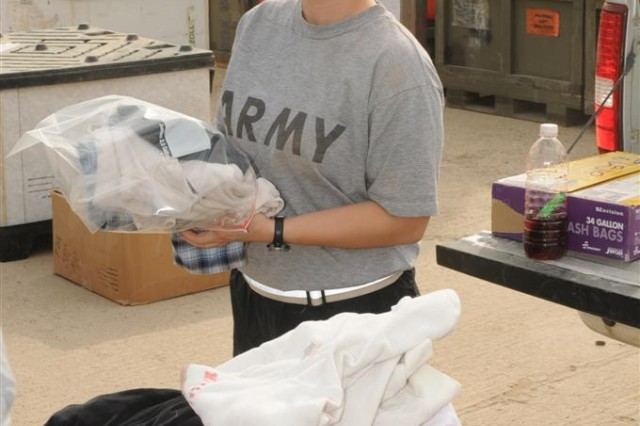 Staff Sgt. Rose L. Mattie, the operations noncommissioned officer in charge with the 3666th Support Maintenance Company, 541st Combat Sustainment Support Battalion, 15th Sustainment Brigade, 13th Sustainment Command (Expeditionary), folds clothing to be handed out during a humanitarian aid mission March 14 at Contingency Operating Base Taji, Iraq. Mattie, a Phoenix native, planned and coordinated the event.