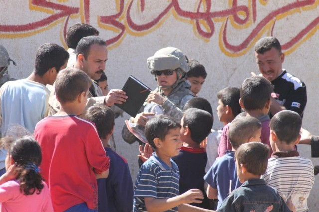 Staff Sgt. George T. Huerta, an Allied Trades foreman with the 3666th Support Maintenance Company, 541st Combat Sustainment Support Battalion, 15th Sustainment Brigade, 13th Sustainment Command (Expeditionary) and a Scottsdale, Ariz., native, hands out clothes to Iraqi children during a humanitarian mission March 21 near Contingency Operating Base Taji, Iraq.