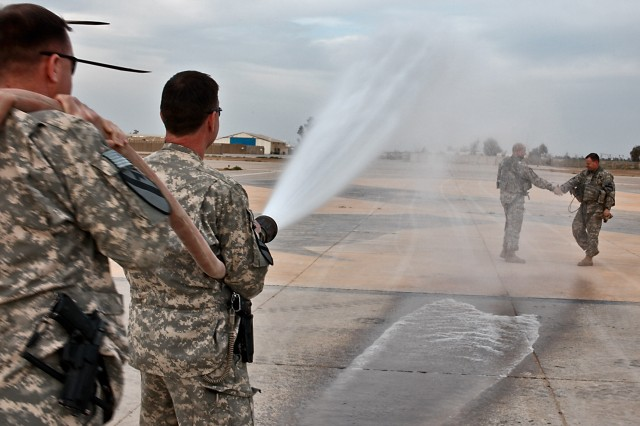 CAMP TAJI, Iraq - Keeping with aviation tradition, Chief Warrant Officers Dan Wallace (background right), from Fort Hood, Texas, the brigade tactical operations officer, and Donald Washabaugh, from Collingswood, N.J., the brigade aviation maintenance officer, shake hands while getting hosed down March 25 by fellow aviators Chief Warrant Officers Michael Reese (foreground right), from Copperas Cove, Texas, the brigade standardizations instructor pilot, and Scott McLendon, also from Copperas Cove, the brigade safety officer. All are in 1st Air Cavalry Brigade, 1st Cavalry Division, U.S. Division-Center. Wallace and Washabaugh have a combined 55 years of service and 8,000-plus flight hours. Both are also taking jobs where they will no longer pilot aircraft.