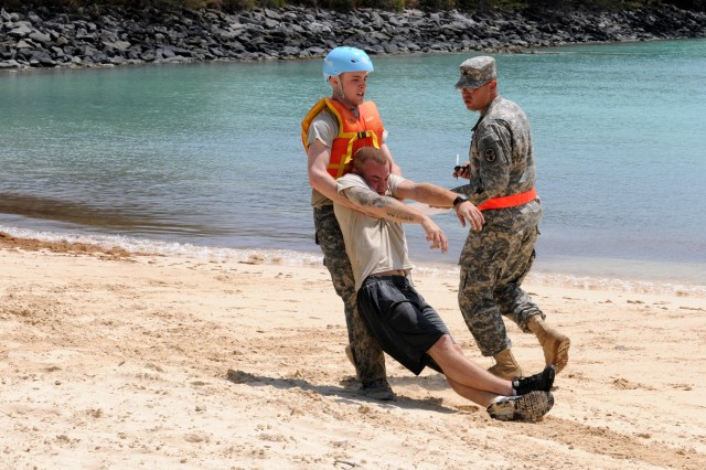"""Specialist John Evans, Munson Army Health Center x-ray technician, Fort Leavenworth, Kan., Western Regional Medical Command and winner of this year's Soldiers competition moves a injured civilian to safety during the mystery event at the Army Medical Command's """"Best Warrior"""" competition that was hosted by Pacific Regional Medical Command and held in Hawaii for the first time ever. The competition extended over a five day period and tested the Soldiers ability to withstand physically challenging events, while maintaining the mental edge to continue to perform effectively March 13-19."""