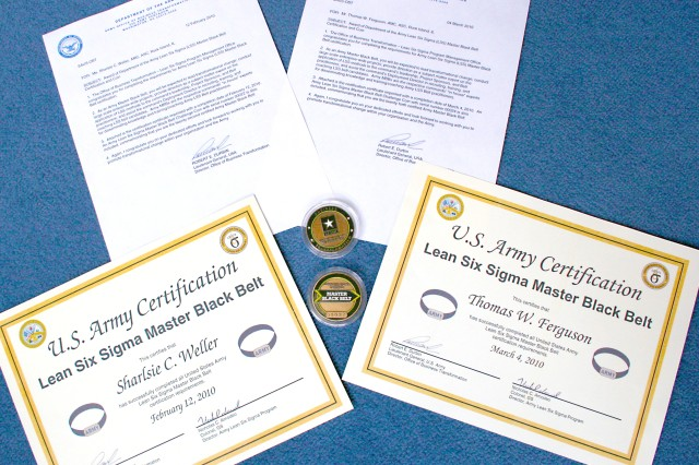 """Shown are the mementos bestowed upon Sherry Weller and Thomas Ferguson, process improvement specialists with ASC Headquarters' Command Assessment and Continuous Improvement Office at Rock Island Arsenal. For their extraordinary efforts, MBBs receive a certificate and letter signed by the director, Office of Business Transformation, Lt. Gen. Robert Durbin, and a Lean Six Sigma Master Black Belt Challenge Coin with their serial numbers """"00022"""" (Weller) and """"00024"""" (Ferguson)."""