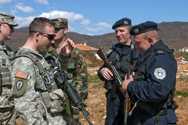 Staff Taylor Smith, Thompson, N.D., discusses the M-4 Carbine rifle during a stop on a joint patrol near the FYROM border.