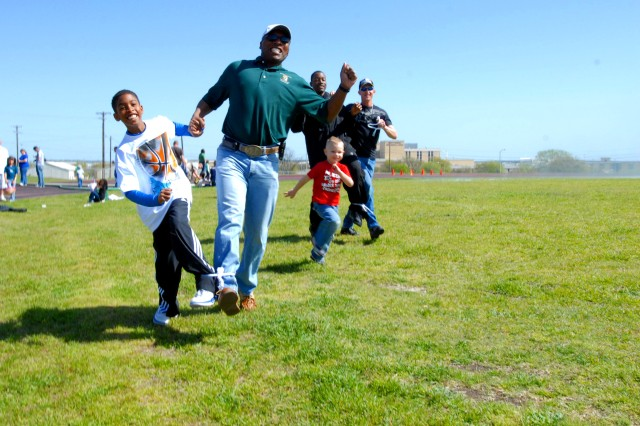 Ten-year-old Ronald Kirklin II won a three-legged race with his father, Col. Ronald Kirklin, the brigade commander, at the 4th Sustainment Brigade Easter Egg Hunt Mar. 27 at Hood Stadium on Fort Hood, Texas. (U.S. Army photo by Pfc. Amy M. Lane)