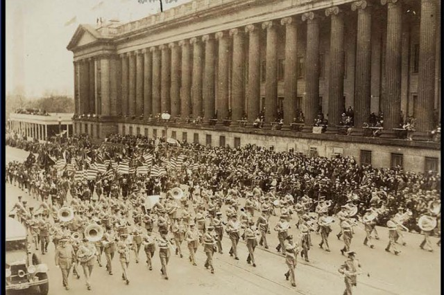 The U.S. Army Band marches up 15thStreet alongside the U.S. Treasury Building.
