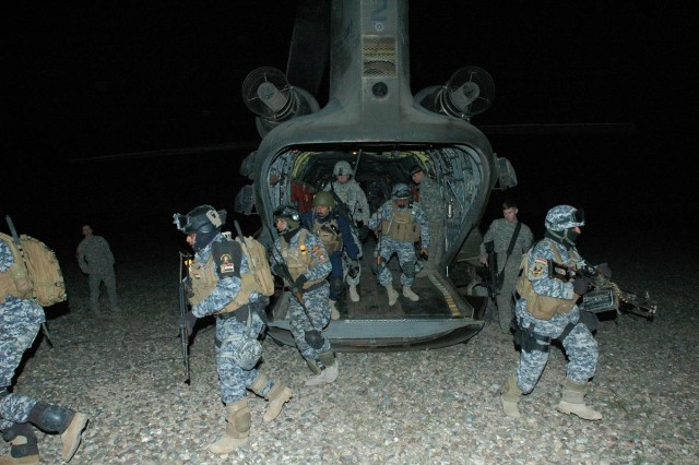 Iraqi Police and Soldiers from Company B, 2nd Battalion, 32nd Field Artillery Regiment, 4th Infantry Brigade Combat Team, 1st Infantry Division, rehearse exiting a CH-47D Chinook helicopter prior to an insertion at Contingency Operating Location Danger, near Tikrit, Iraq, Feb. 25. The aircraft belongs to 3rd Battalion, 25th General Support Aviation Battalion, Task Force Wings. (Photo by:  Sgt. 1st Class Tyrone C. Marshall, 25th Combat Aviation Brigade Public Affairs)