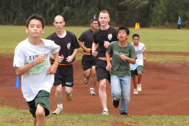 Two Soldiers from 2nd Battalion, 35 Infantry Regiment, 3rd Brigade Combat Team, 25th Inf. Division run with Wahiawa Middle School students in a 1.5 mile fun run March 24. (courtesy photo)