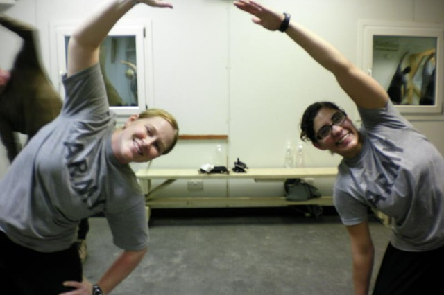 1st Lt. Stephanie Edinger and Spc. Denicia Dodd, with the 363 Military Police Company, conducting oblique side stretches.