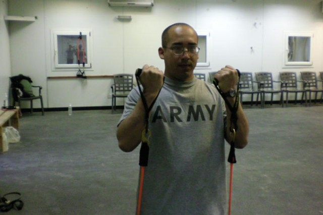 Spc. Dana Drake, with the 1083rd Transportation Company conducting curls with the resistance bands.